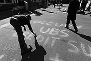 Occupy movement action on Paradeplatz, symbolic centre of the Swiss banking industry, chalking slogans on the pavement 'Occupy UBS Credit Suisse & Wall Street', the country's two largest banks. The banks vaults are said to lie under the square.