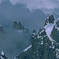 Summits of the French Alps poke through clouds above the Chamonix Valley, France.
