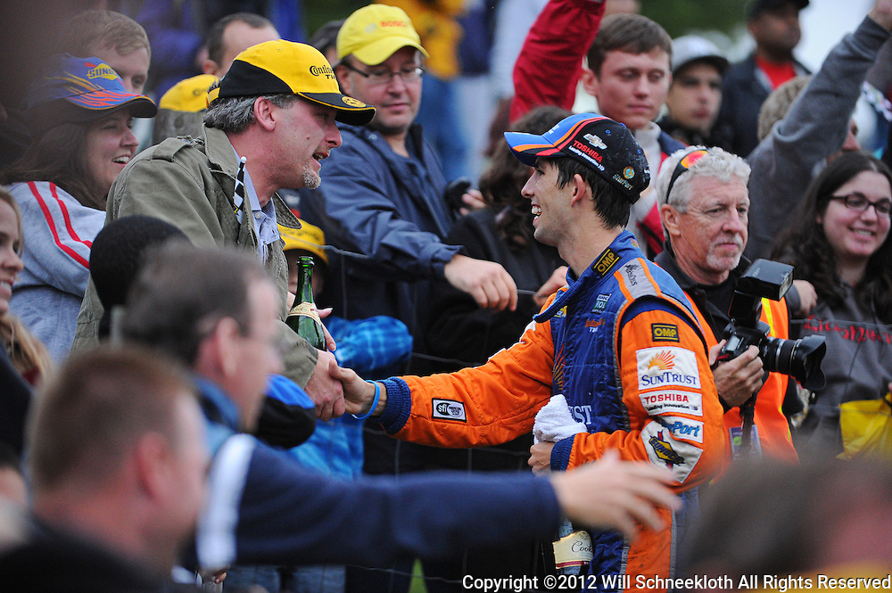 SunTrust Chevrolet Corvette DP driver Ricky Taylor shakes hands with fans surrounding the podium following his victory in the Grand-Am Rolex Sports Car Series Championship Race at Lime Rock Park in Lakeville, Conn.
