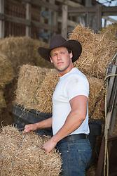 sexy cowboy working in a hay barn