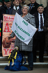 Royal Courts of Justice, London, February 8th 2017. As day two for the appeal hearing for 'Marine A' - Sgt Alex Blackman draws to a close, retired Marines and supporters gather on the steps of the High Court as his wife Claire emerges from the building. PICTURED: A supporter waits on the steps of the High Court.