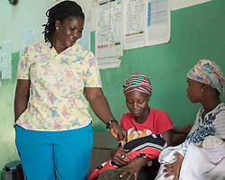 4 November 2019, Vriginia, Liberia: Nurse Helena Bridges welcomes two mothers looking to get vaccines for their newborn children. Helena Bridges serves as head nurse at Ricks Clinic, a part of Ricks Institute. For seven years, she has provided healthcare for students experiencing sicknesses such as Malaria or ordinary colds. The Liberia Baptist Convention runs Ricks Institute, a day and boarding school for currently 496 students from kindergarten up through 12th grade.