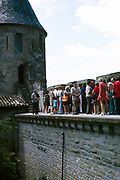Walls, tower and ramparts UNESCO World Heritage Site, fortified city of Carcassonne, France 1973 tourists on guided tour