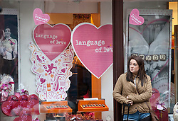 © licensed to London News Pictures. London, UK 13/02/2012. A shopper waits outside a shop which sells Valentine's Day gifts on the day before Valentine's Day in Oxford Street, London. Photo credit: Tolga Akmen/LNP