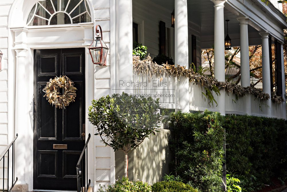 A historic home decorated for Christmas with wreaths and roping on King Street in Charleston, SC.