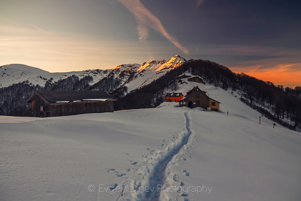 Snow trail leads to a mountain hut