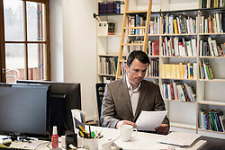 Mature businessman reading papers in an office, Bavaria, Germany