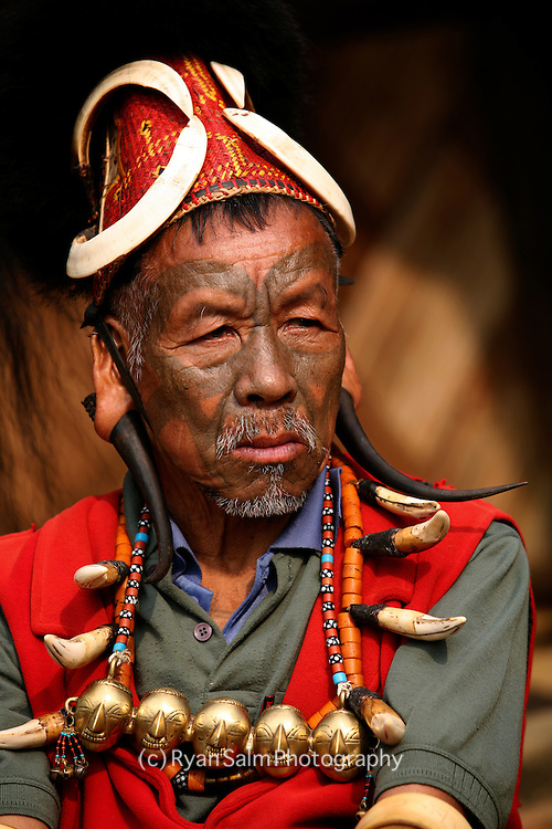 A Naga chief exhibits his tribal facial tattoo's and traditional clothing that date back to the headhunting days in Nagaland.