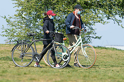 ©Licensed to London News Pictures 14/04/2020  <br /> Greenwich, UK. Two mask wearing cyclists pushing their bikes. Sunny weather in Greenwich park, Greenwich, London as people get out of the house from coronavirus lockdown to exercise. Photo credit:Grant Falvey/LNP
