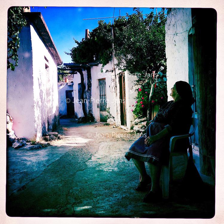 Kreta, Kroustas , 24 juli 2013.<br /> <br /> Een straatje in het bergdorpje Kroustas even ten Zuiden van Kritsa in het Noord Oosten van Kreta.<br /> Summer holiday on the Greek island of Crete. Streetview. Woman resting.