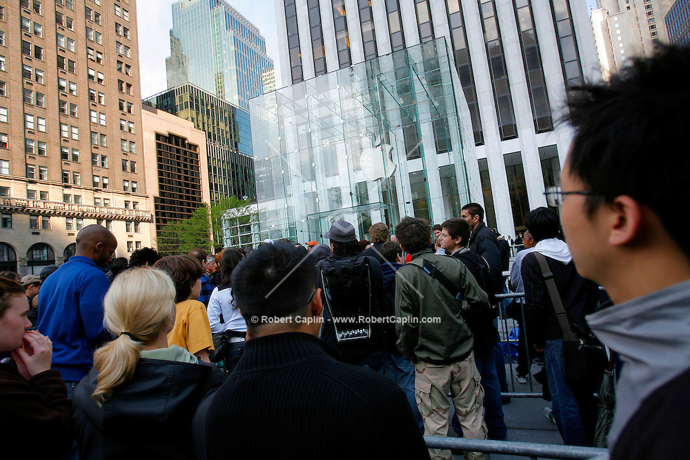 Some of the first customers wait in line in front of the new Apple Store in New York on Friday, May 19, 2006. Apple Computer Inc., maker of the iPod music player, opened a 24-hour subterranean store in New York City, marking five years in retailing with an outlet built beneath a 32-foot glass cube.