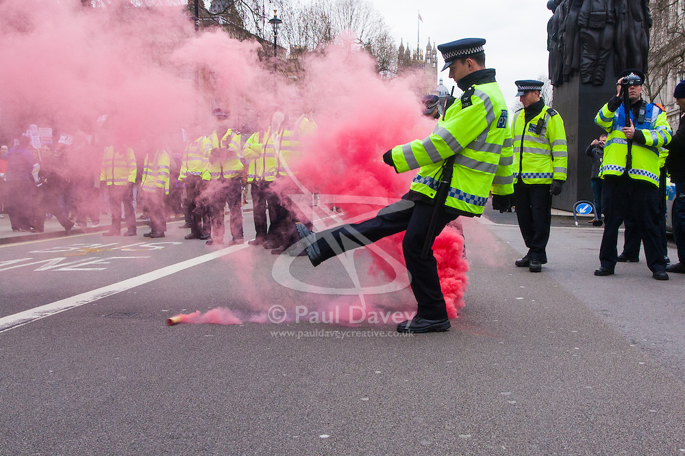 Whitehall, London, April 4th 2015. As PEGIDA UK holds a poorly attended rally on Whitehall, scores of police are called in to contain counter protesters from various London anti-fascist movements. PICTURED: A police officer kicks away a smoke bomb thrown by anti-fascists as they attempt to break through police lines to attack the few men and women attending the PEGIDA rally.