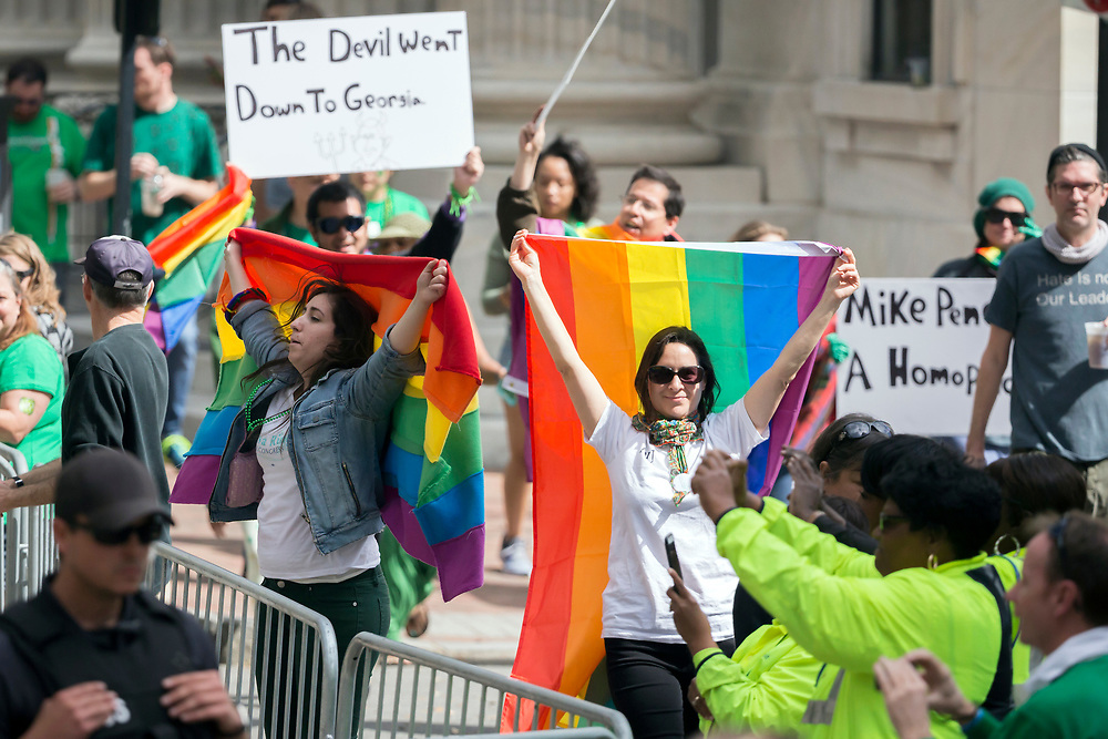 A group of LBGTQ protesters jeer Vice President Mike Pence as he walks the Savannah St. Patrick's Day parade, Saturday, March 17, 2018, in Savannah, Ga. (AP Photo/Stephen B. Morton)