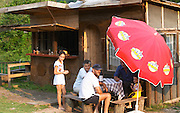 A ramshackle road side roadside bar with sun shade umbrellas. Two men and an old woman sitting drinking wine and a young girl and small boy. Near Dupilo, Golubovic Montenegro, Balkan, Europe.