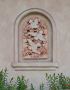 Wall sculpture on Spanish-style stucco wall in Carmel, California depicts birds in flight