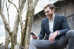 Mid adult businessman using mobile phone outside and smiling, Bavaria, Germany