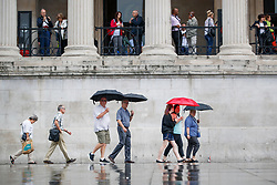© Licensed to London News Pictures. 27/06/2017. London, UK. People take shelter from the rain under umbrellas in Trafalgar Square, London on Tuesday, 27 June 2017. Photo credit: Tolga Akmen/LNP