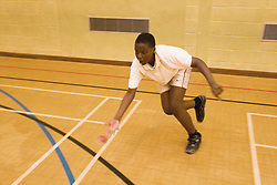 Secondary school student catching a ball during a game of indoor cricket in the school sports hall,