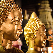The faces of two Buddha statues at Wat Mai Suwannaphumaham.  Wat Mai, as it is often known, is a Buddhist temple in Luang Prabang, Laos, located near the Royal Palace Museum. It was built in the 18th century and is one of the most richly decorated Wats in Luang Prabang.