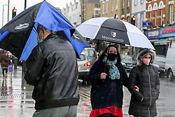 © Licensed to London News Pictures. 02/05/2021. London, UK. People shelter from heavy rain beneath umbrellas in north London. Windy and wet weather is forecasted for the bank holiday Monday. Photo credit: Dinendra Haria/LNP