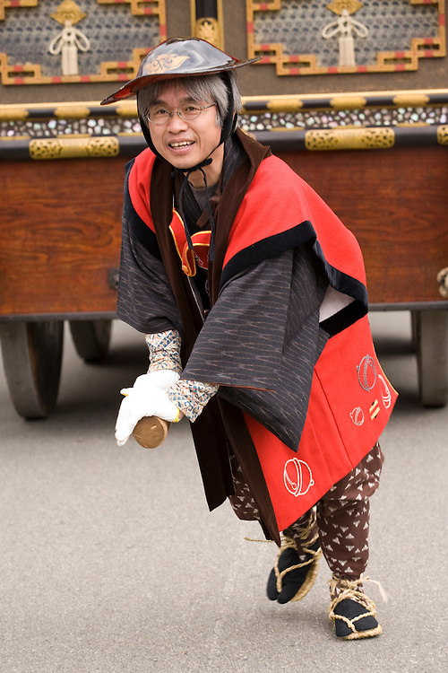 Asia, Japan, Gifu prefecture, Takayama (also known as Hida-Takayama), man in traditional jacket pulls elaborate festival float (yatai)  through streets in Gonjunko Procession during Sanno Festival of Hie Jinja Shrine, held annually in April.