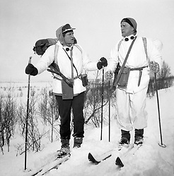 File photo dated 02/03/65 of actors Richard Harris (left) and Kirk Douglas ploughing through heavy snow in Norway while on location for the war film The Heroes of Telemark. Douglas is celebrating his 100th birthday today.