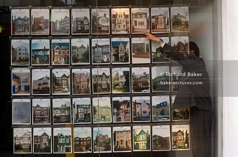 In the window of a London estate agency, we see many properties in various styles and ages for sale. A sales executive swaps some of the pictures as some sell or perhaps, are taken off the market by their vendors.