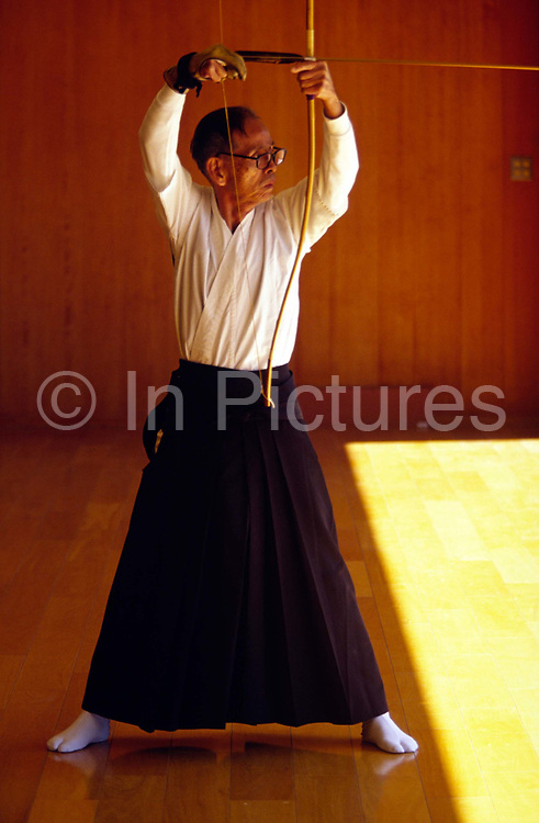 An elderly Kyodo practitioner draws his bow, Kyoto dojo.Kyudo is a modern Japanese martial art derived from ancient Samurai archery, heavily influenced by Zen Buddhist philosophy.