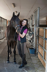 Mature woman stroking her brown horse in stable and smiling, Bavaria, Germany