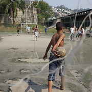 Local boys play football on a run down concrete pitch near the Carnival parade ground in Rio de Janeiro.. Rio de Janeiro,  Brazil. 17th September 2010. Photo Tim Clayton.