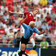 Uruguay's Dario Silva and Denmark's Martin Laursen battle for the ball