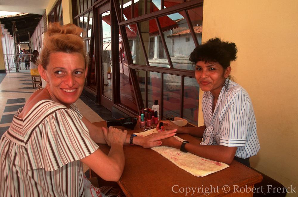 CUBA, ISLE OF YOUTH Nueva Gerona, main street, with beautician doing nails