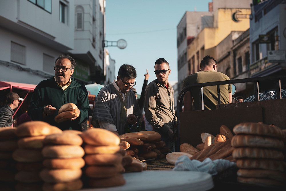 Assilah, Morocco - May 18, 2018: Bread for sale on the street in the coastal city of Assilah. In the background, a man raises his middle finger.