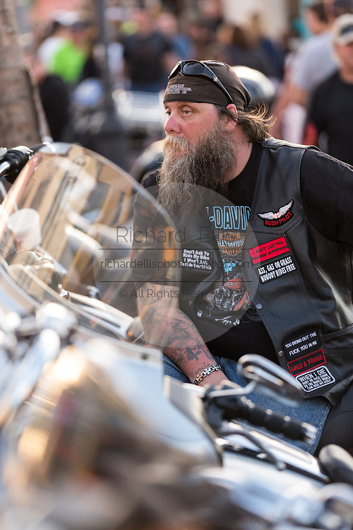 A leather clad biker watches the parade of motorcycles down Main Street during the 74th Annual Daytona Bike Week March 8, 2015 in Daytona Beach, Florida. More than 500,000 bikers and spectators gather for the week long event, the largest motorcycle rally in America.