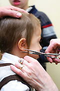 "Shalev, Young Jewish boy of three having his first ritual haircut called Upsherin (Yiddish: lit. ""shear off"") or Chalaka"