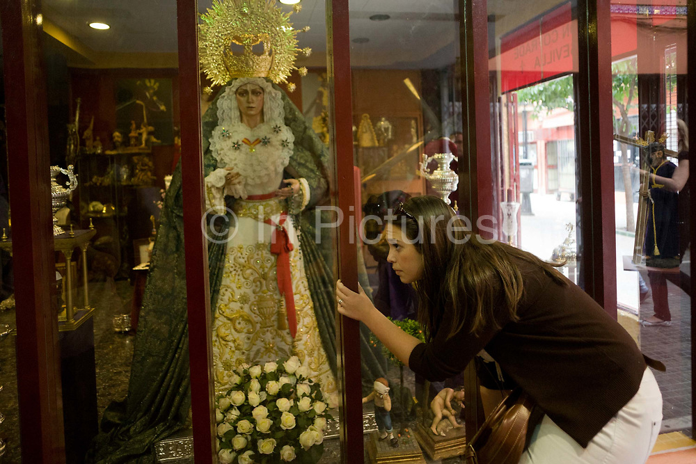 A young Spanish woman and a Virgin Mary mannequin in a shop window during the Semana Santa festivals. In a scene showing the morals and ethics of the Catholic Church within Spanish Society, the young lady shows an ambiguous devotion to the the Madonna while to the far right the figure of a Jesus carrying the cross appears to merge with another woman walking in the street. All of this takes place during Seville's annual Semana Santa Easter passion processions. Some 60 processions are scheduled for the week, from Palm Sunday through to Easter Sunday morning. The climax of the week is the night of Holy Thursday, when the most popular processions set out to arrive at the Cathedral on the dawn of Good Friday, known as the madrugá.