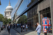 With the dome of St. Paul's Cathedral at the end, lunchtime City workers walk past the Union Jack-themes telephone kiosk in celebrity chef Gordon Ramsey's restaurant Bread Street Kitchen on (the former Roman thoroughfare) Watling Street, in the City of London, the capital's financial district (aka the Square Mile), on 22nd August 2019, in London, England.