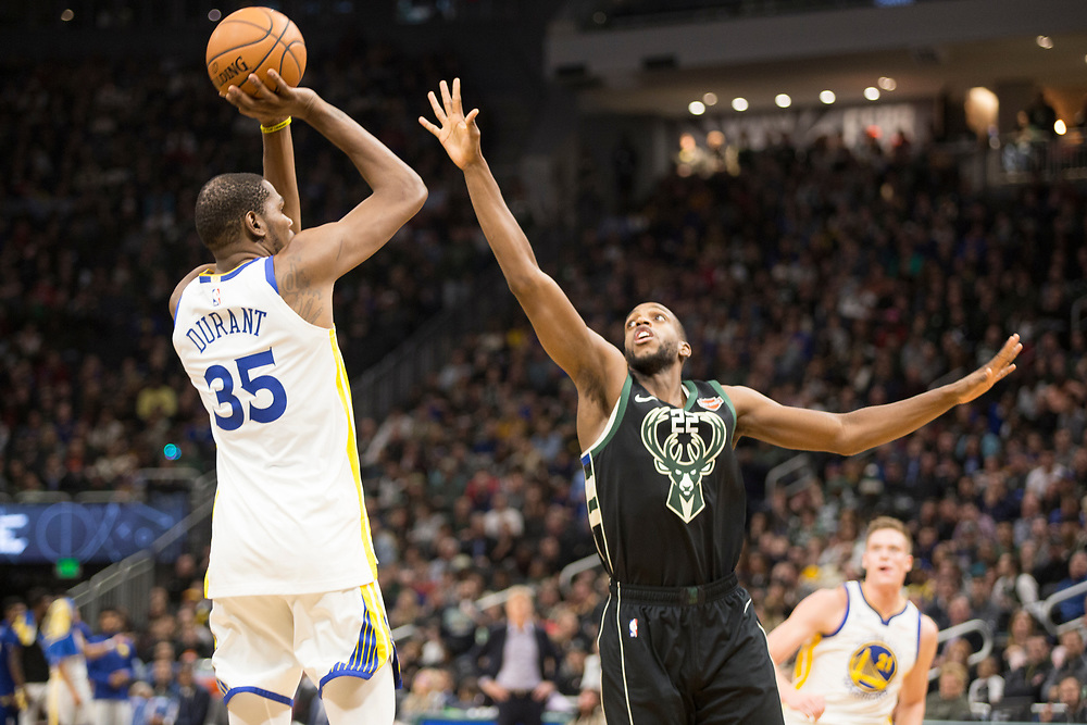 Kevin Durant shoots from long range as Khris Middleton defends during the Golden State Warriors' away game against the Milwaukee Bucks on December 7, 2018.