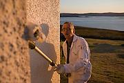 Decorator rolls emulsion paint in warm evening sunshine on to hilltop cottage wall in hamlet of Hallin, Waternish, Skye