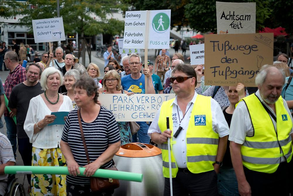 An die hundert Menschen protestieren in Berlin auf einer Demonstration des Fachverband Fußverkehr Deutschland (FUSS) für die Rechte von Fußgängern, für freie Gehwege und gegen Falschparker und gegen Fahrräder und E-Tretroller, die auf Gehwegen fahren und stehen und liegen. Demonstrantin mit Schild: Parkverbot für Leihräder und Roller auf den Gehwegen. <br /> <br /> [© Christian Mang - Veroeffentlichung nur gg. Honorar (zzgl. MwSt.), Urhebervermerk und Beleg. Nur für redaktionelle Nutzung - Publication only with licence fee payment, copyright notice and voucher copy. For editorial use only - No model release. No property release. Kontakt: mail@christianmang.com.]