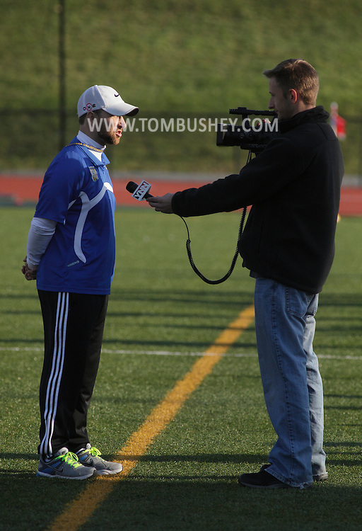 Middletown, New York - A cable television reporter, at right, interviews a high school boys' soccer coach after the New York State Class AA championship game on Nov. 20, 2011.