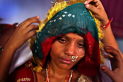 Fifteen-year-old Sarita's face, covered in tears and sweat, is covered before she is sent to her new home with her groom. The previous day, she and here young sister, Maya, 8, were married to another set of siblings  on the Hindu holy day of Akshaya Tritiya, called Akha Teej in North India. Despite legislation forbidding child marriage in India (Child Marriage Restraint Act-1929) and the much more progressive Prohibition of Child Marriage Act (2006) and many initiatives to prevent child marriage, marrying children off at a very tender age continues to be accepted by large sections of society.