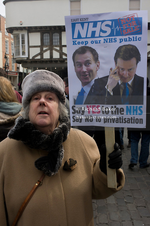 An prosperous-looking elderly middle-class voter who represents so-called middle-England, protests over coalition plans over the NHS, holding a placard in Butter Market in the centre of Canterbury. Health Secretary Jeremy Hunt and Conservative (Tory) Prime Minister David Cameron are parodied on the poster urging them to keep the country's National Health Service out of private hands, to keep it as a government organisation, run by Hunt and overseen by his boss, Cameron. The town of Canterbury hosted the enthronement of the Church of England's new Archbishop, allowing students and this well-dressed tady to voice their concerns.