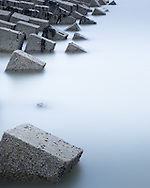 Concrete cubes seem to be slowly falling into the sea. These are harbour defences in the sea at Shoreham near Brighton. Each concrete cuebe is about a metre on a side. They had gradually broken away from the regular lines they had been set in to collapse into a disorderly mess. A very long exposure gives the smooth water texture. © Andrew Tobin www.tobinators.com