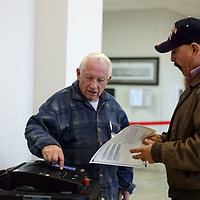 Volunteer Martin Link directs Tomás Aguilar to feed his ballot in to the machine to cast his vote for the school board at McKinley County Courthouse in Gallup Tuesday.