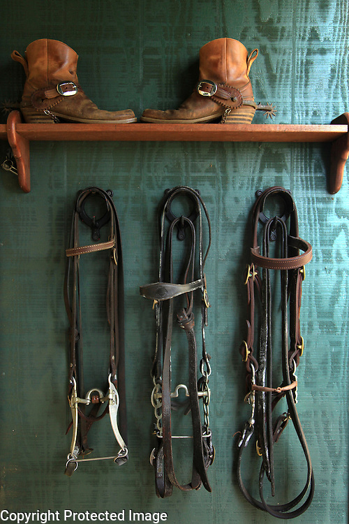 """Cowboy boots and tack are on display outside veterinarian Dr Billy Bergin's Paniolo Preservation Society offices in Waimea, Hawaii.  Dr. Bergin has long treated the Hawaiian cowboys' horses and cattle and founded the Paniolo Preservation Society to promote the preservation of paniolo history and culture.  He has a large collection of historical photographs and items related to the history of cowboy culture in Hawaii. """"There have been cowboys in Hawaii longer than in the west and their history is worth preserving,"""" says Bergin of his reason for founding the preservation society."""