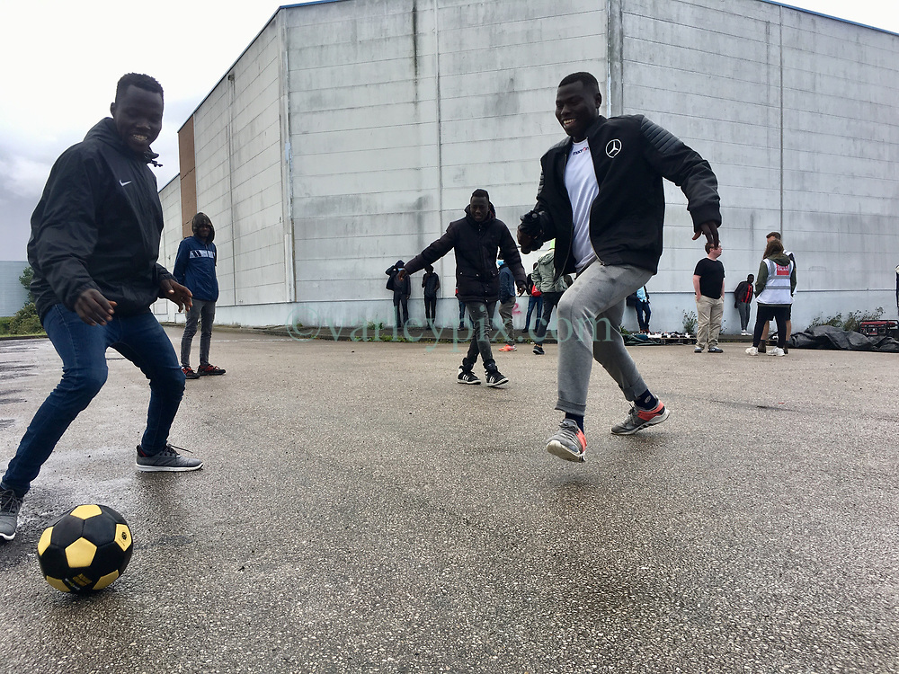 30July2021. Calais, France.<br /> Adam Abdualaziz (rt with white shirt under Mercedes jacket) was recruited from Sudan to play football in Europe where he joined Juventus Crew Alpha in Germany. Sadly he didn't make the cut and is just one of many young men dumped onto the streets of Europe by football clubs. Adam is now a migrant receiving aid from <br /> British founded charity Care4Calais on a morning aid drop where they offer phone charging and food to migrant refugees in Calais. The charity also provides games to help lift their spirits. With police ramping up efforts to make Calais as hostile as possible, many migrants have taken to living in swampy inhospitable terrain spread around the town. <br /> Photo©; Charlie Varley/varleypix.com