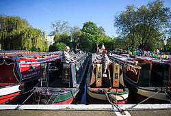 © Licensed to London News Pictures. 05/05/2018. London, UK. Two boat owners stand in the early morning sunshine as the Canalway Cavalcade festival takes place in Little Venice, West London on Saturday,  May 5th 2018. Inland Waterways Association's annual gathering of canal boats brings around 130 decorated boats together in Little Venice's canals on May bank holiday weekend. Photo credit: Ben Cawthra/LNP