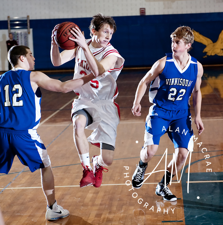 Laconia's Brady O'Neil races past Winnisquam's Alex Evangelo and David Andrus in Saturday's game during Gilford's 35th Annual Holiday Basketball Tournament at Gilford HIgh School.  (Alan MacRae/for the Laconia Daily Sun)