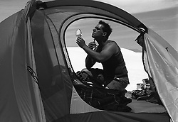 Man at a campsite in New Mexico shaving